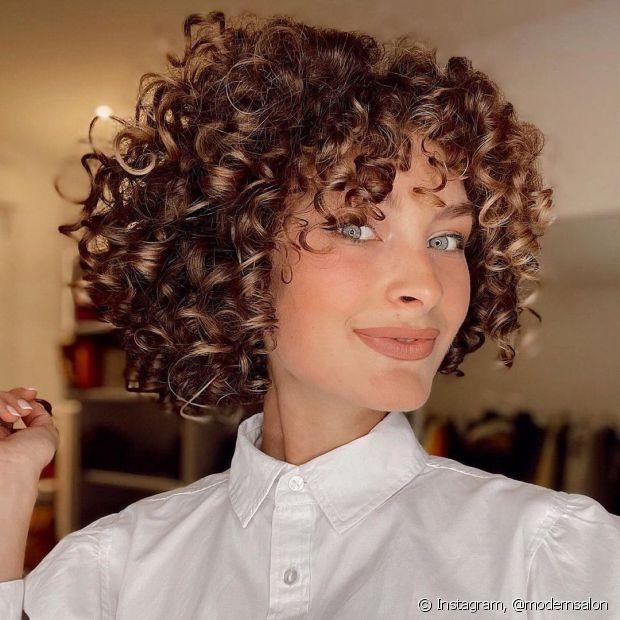Morena iluminada em cabelo cacheado curto: as iluminações valorizam o formato dos cachos. (Fotos: Instagram @modernsalon)