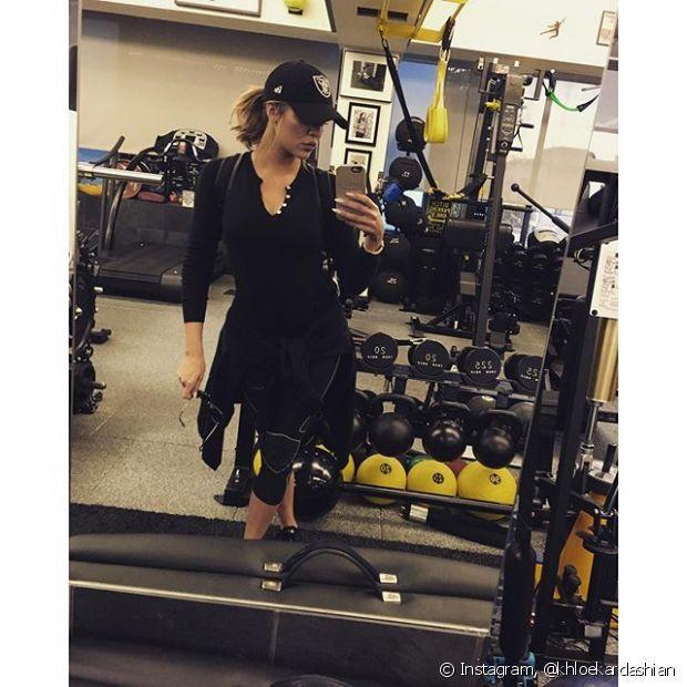 Khloe Kardashian usa um boné para proteger os cabelos do suor durante o treino