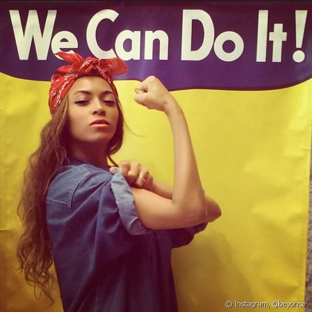 Beyoncé amarrou um lenço vermelho nos cabelos e uma blusa jeans para reproduzir o clássico cartaz 'We Can do It'