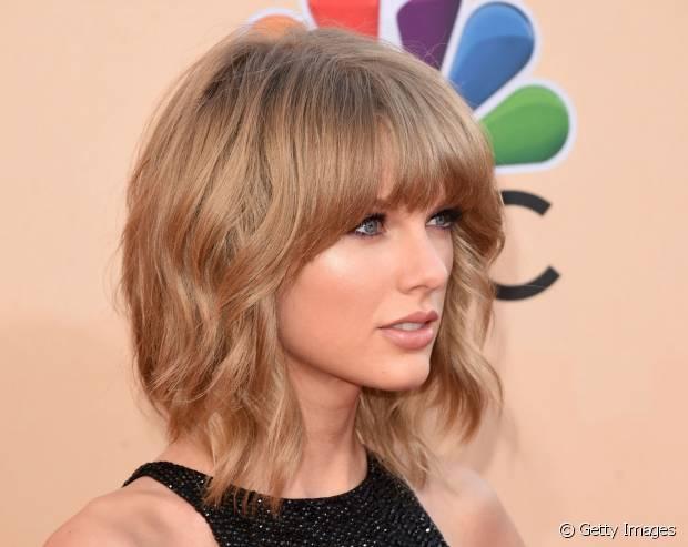Taylor Swift aderiu ao corte com franja reta e finalização ondulada