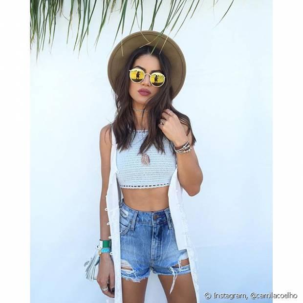A blogueira Camila Coelho investiu em top de crochê, short jeans e colete para curtir o Coachella