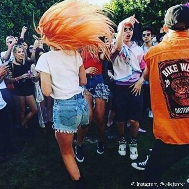 Para o primeiro dia do Coachella, Kylie Jenner foi com um look simples: t-shirt branca e shor jeans, mas completou a produção com uma precua longa laranja