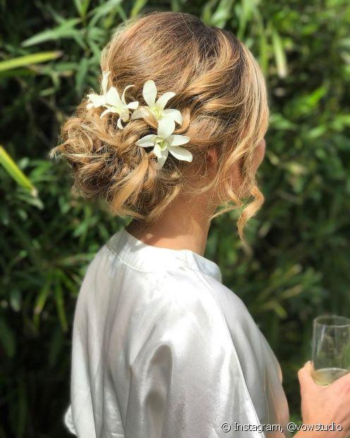 Adicionar ondas com detalhes de flores no penteado da noiva vai destacar o cabelo para as fotos de maneira sofisticada