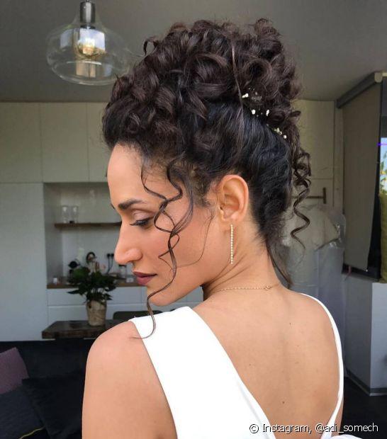 Os coque altos com mechas soltas são ótimas opções de penteados para cabelos cacheados para casamento. (Foto: Instagram @adi_somech)