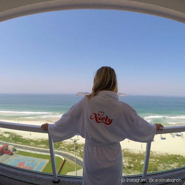 Carolina Tognon posa com o roupão da Niely na sacada do hotel