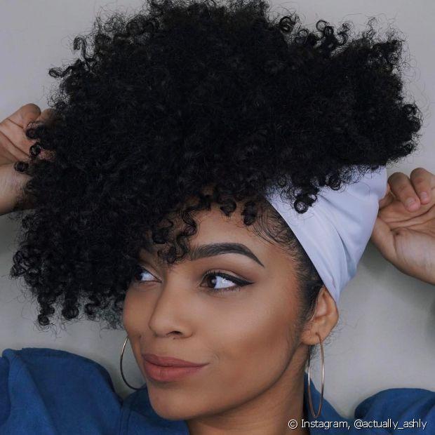 Prender os cabelos cacheados para o alto e completar co visual com um lenço é estilo na certa