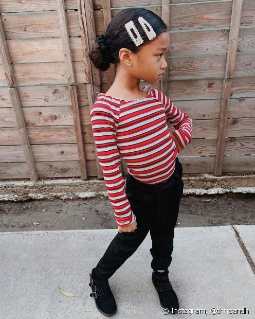 O coque baixo em cabelo cacheado infantil pode ser incrementado com presilhas e uma pose (Foto: Instagram @chrisandh)