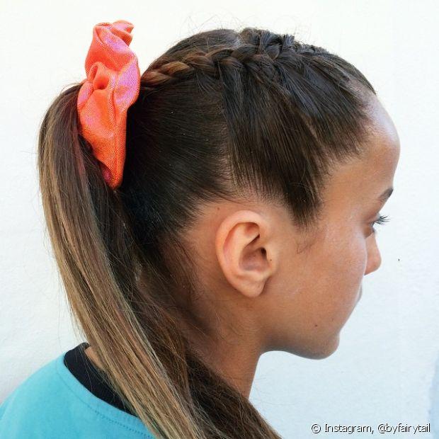 Crie uma trança com mechas do início do cabelo antes de prender o fios em rabo de cavalo