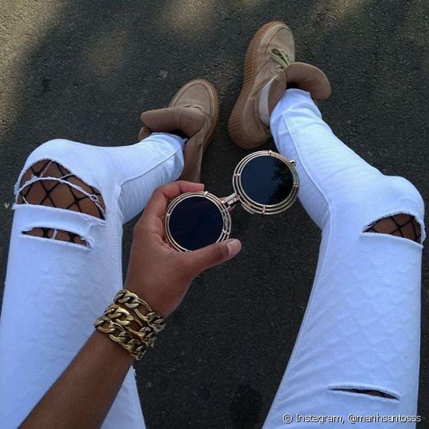 A meia arrastão pode aparecer apenas em detalhes no look, através dos rasgos da calça jeans