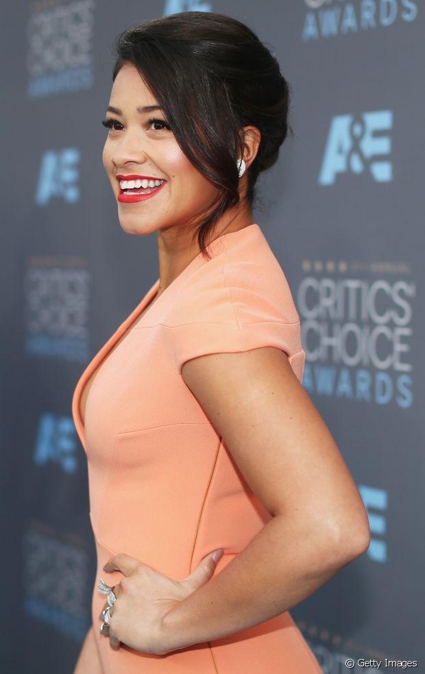 A atriz Gina Rodriguez optou por deixar o franjão solto num look com coque banana