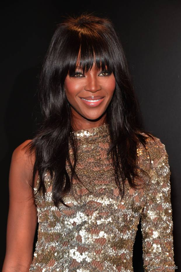 Naomi Campbell aposta nos alongamentos de cabelo para compor o look de fios compridos e franjinha