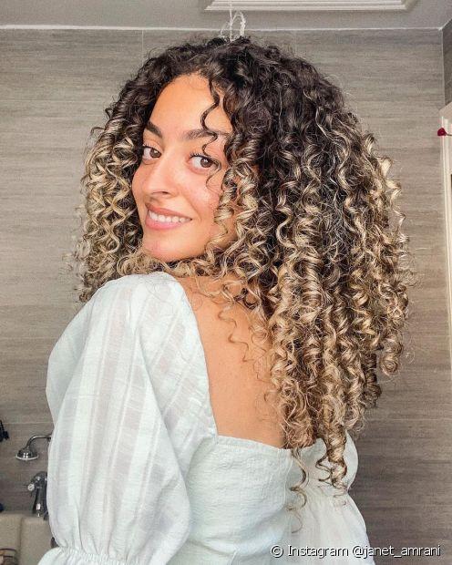 O visual morena iluminada em cabelos cacheados pode ser alcançado com diferentes técnicas de coloração (Foto: Instagram @janet_amrani)