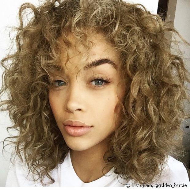 O cabelo cacheado loiro escuro é uma aposta segura para todos os tons de pele