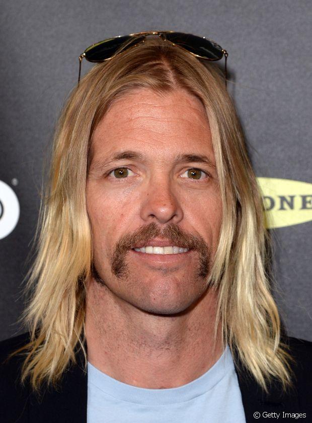 """Taylor Hawkins, baterista do Foo Fighters, usa os cabelos com visual """"surf"""", loiros, grandes e com as pontas mais claras"""