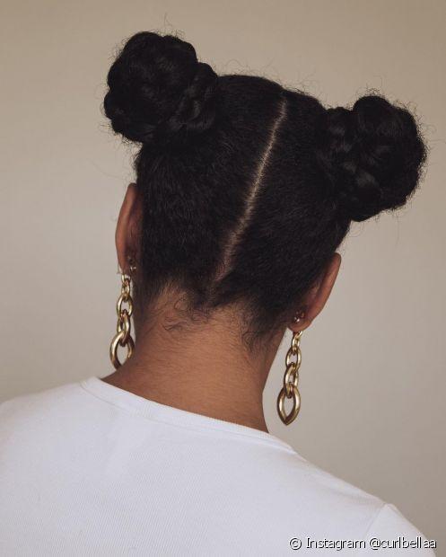 O coque duplo no cabelo crespo garante estilo e pode ser incrementado com tranças na base do coque (Foto: Instagram @curlbellaa)