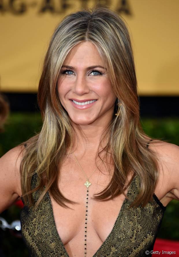 Jennifer Aniston tem os cabelos desfiados somente na frente e uma franja longa e dividida ao meio, ideal para destacar a moldura do rosto