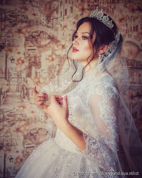 Os cachos com visual ondulado deixam o look da noiva bem elegante junto com o véu