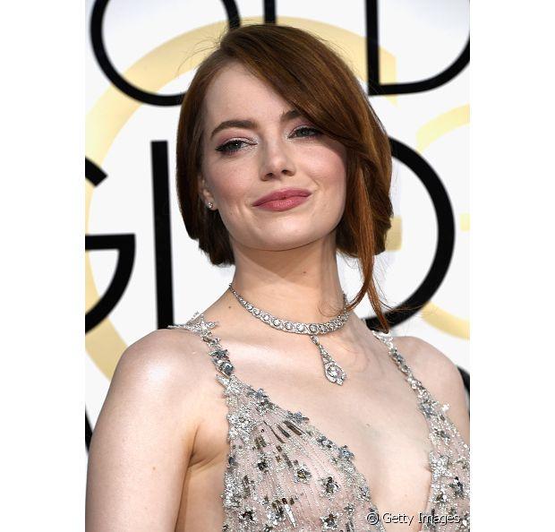 Emma Stone é fã do franjão lateral e um coque despojado